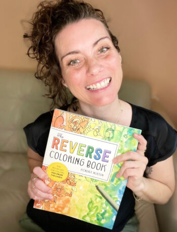 Artist and author Kendra Norton holding her book, The Reverse Coloring Book